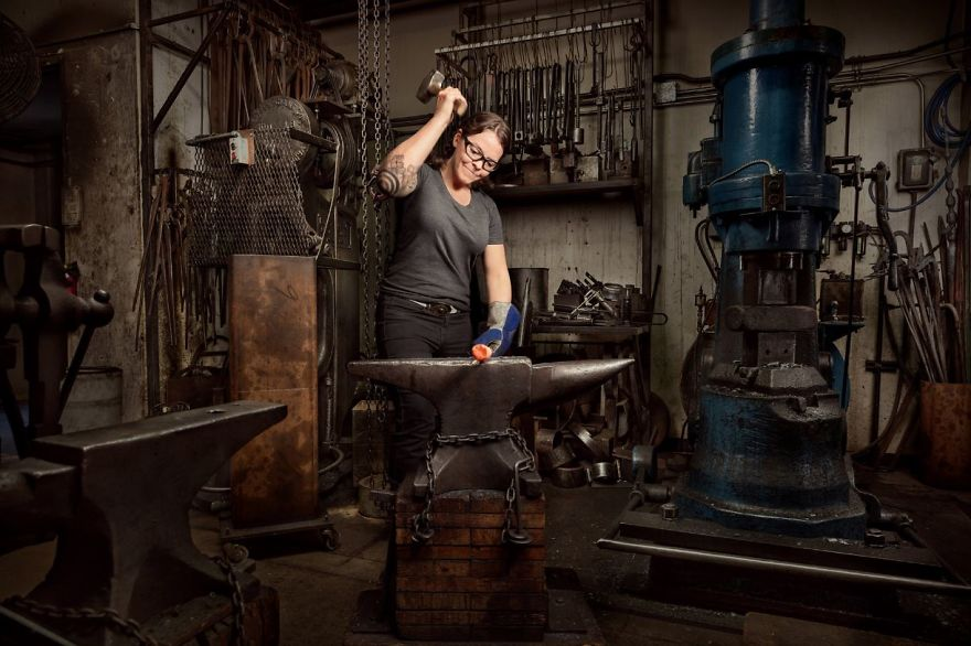 A blacksmith hammers a hot piece of steel on her anvil.