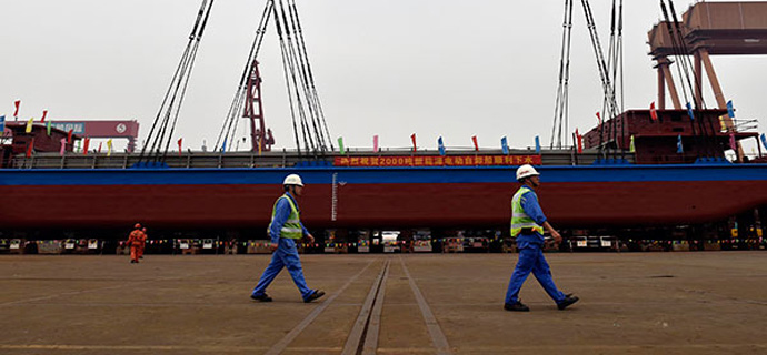Two workers walk in front of China's electric ship.