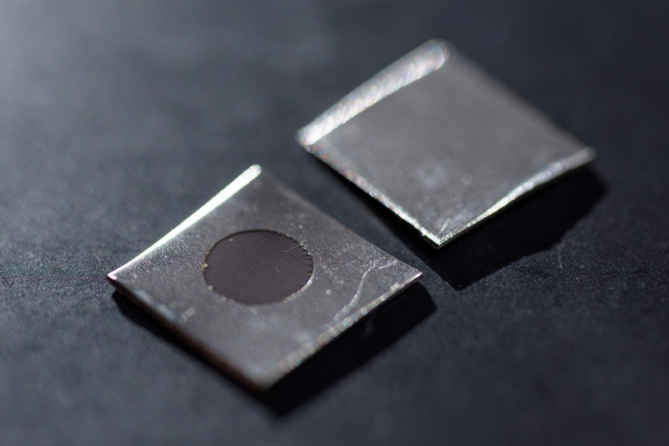 Two small square pieces of stainless steel that are nanotextured.