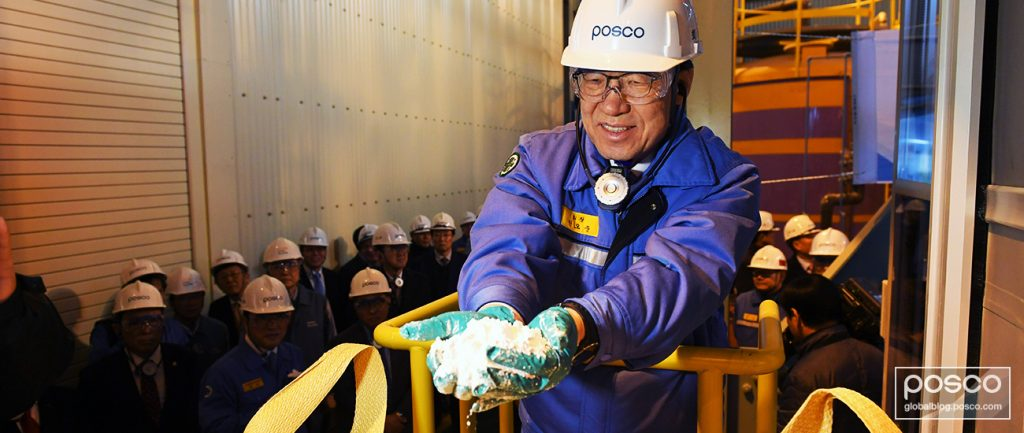 POSCO CEO Ohjoon Kwon holding lithium during his visit to PosLX with employees watching on.