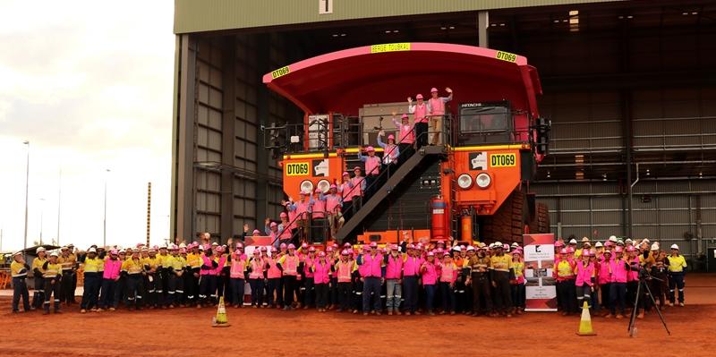 로이힐 광산 직원들이 5,500만톤 규모 최단시간 구축(Fastest ramp up to 55Mtpa in Australia)이라는 축하 배너와 함께 기념 사진을 찍는 모습