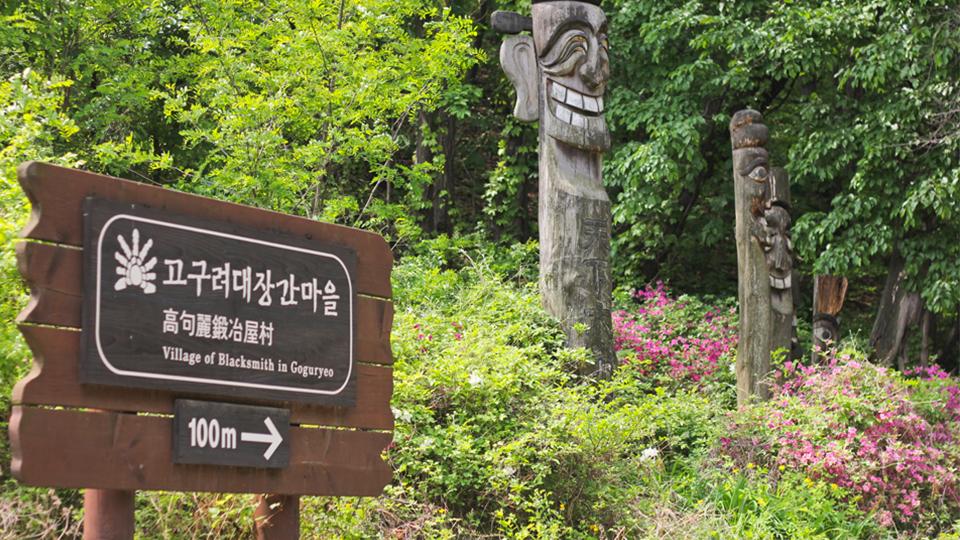 고구려대장간마을의 입구표지판 모습. 나무로 된 표지판에 고구려대장간마을이라고 각각 한국어, 한문, 그리고 영어로(Village of Blacksmith in Gpguryeo) 적혀있고, 하단에는 오른쪽을 향하는 화살표 그림과 함께 100m라고 적혀있다.