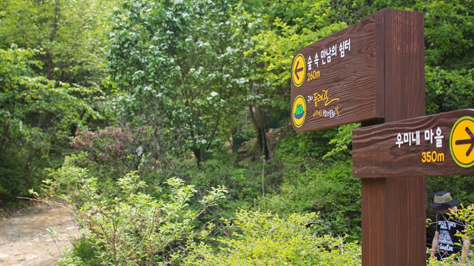 고구려 대장간 마을 아차산 둘레길 입구 표지판 모습. 나무 표지판에 오른쪽 방향의 화살표와 함께 우미내 마을 350m라고 적혀있고, 왼쪽 방향의 화살표화 함께 숲 속 만남의 쉼터 260m라고 적혀있다.