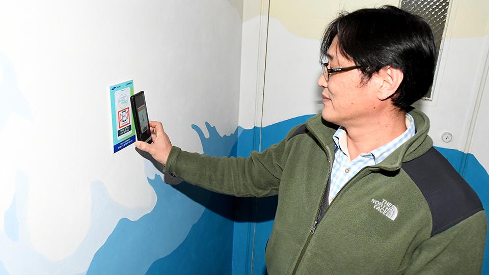 포스코센터 내 걷기왕으로 뽑힌 방주호과장이 NFC 보드에건강계단 앱을 스캔하고 있는 모습
